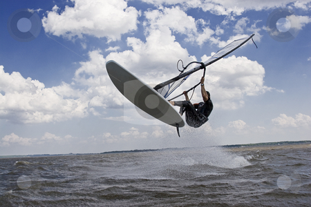 Windsurfer flying in the air stock photo, Windsurfer doing a jump trick in the water and catching lots of air by Yann Poirier