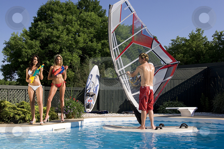 Windsurfer in pool stock photo, Windsurfer in a pool with two women in bikini with water gun by Yann Poirier