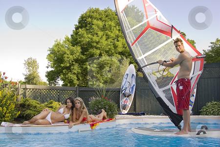 Windsurfer in pool stock photo, Windsurfer in a pool with two women tanning by Yann Poirier