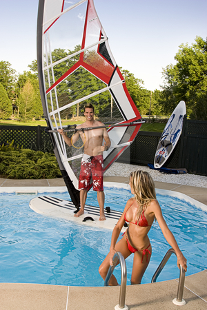 Windsurfer in pool stock photo, Windsurfer in a pool with a women in bikini coming out of the water by Yann Poirier