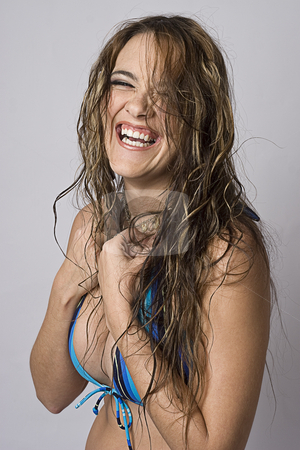 Wild hair lauging stock photo, Women wearing a strip blue bikini trying to hide herself, laughing her head off with her hair all wild by Yann Poirier