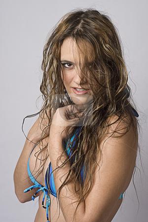 Feral women stock photo, Women wearing a strip blue bikini trying to hide herself with feral expression by Yann Poirier