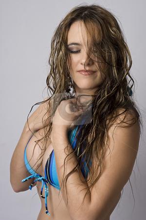 Shy girl in bikini stock photo, Women wearing a strip blue bikini trying to hide herself by Yann Poirier