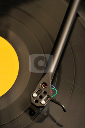 Turntable stock photo, Close-up image of a turntable playing a record with a yellow label by Andreas Karelias
