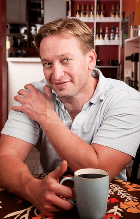 Handsome man with cup of coffee stock photo, Handsome man in coffee house with blue mug by Scott Griessel