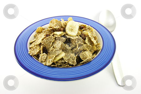 Bran Flakes in a Blue Bowl stock photo, Crunchy delicious looking bran flakes in a blue bowl with a spoon on a white background by Keith Wilson