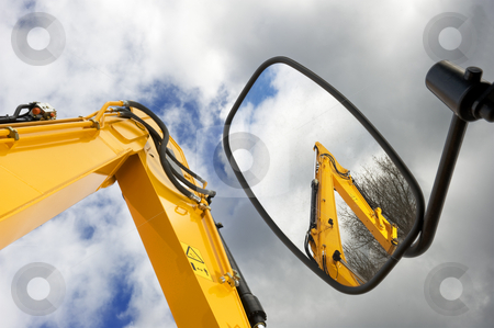 Mechanical arms stock photo, Earth moving machines and forklift arms, one reflected in a side mirror, against a moody sky by Corepics VOF