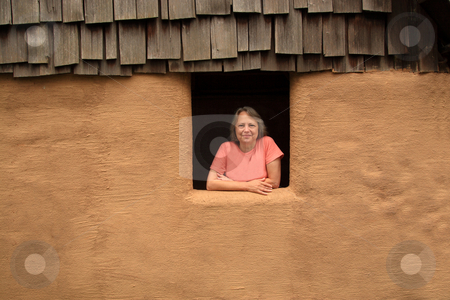 Woman In The Window stock photo, Middle-aged woman leaning out of an adobe hut window into the sunlight. by Jack Schiffer