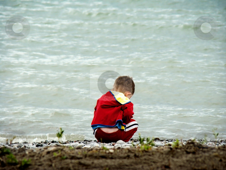 Little boy playing in lake stock photo, little boy is playing by the shore of the lake by CHERYL LAFOND