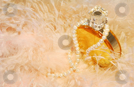 Feathers, necklace and perfume stock photo, Picture of a perfume bottle with a pearls necklace around it, sitting among feathers from a woman's wardrobe. Room for text by Andreas Karelias