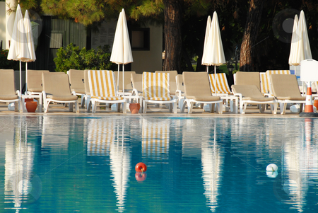 Swimming pool in hotel resort stock photo, Empty chairs with sunshades by blue swimming pool in summer resort by Julija Sapic