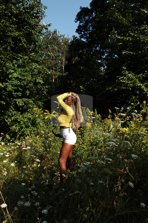 Young Jamaican girl in the woods. stock photo, A young long blond haired Jamaican woman in a bright yellow top and an tight white shorts standing in the woods on a sunny day, with sunglasses. by Horst Petzold