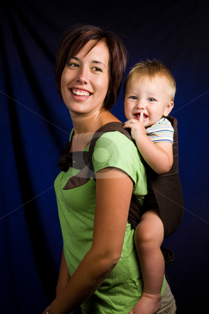 Mother and Son stock photo, A young mother holding her one year old son in a baby carrier. by Travis Manley