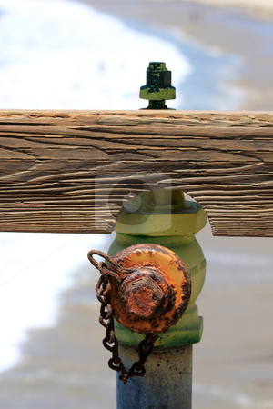 Hydrant stock photo, Hydrant on a pier with the beach in the background. by Henrik Lehnerer