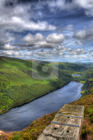 Stretch of Water in Beautiful Valley. stock photo, The larger lake of Glendalough in Co. Wicklow. A wooden sleeper is seen in the foregound and leads the ey to the scenes horizon. by Stephen Kiernan