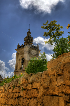 A maltese church tower rising over a stone wall stock photo, An image from Malta showing the steeple of a church rising over a cobbled wall. Incests and birds can be seen flying about and flowers can be seen atop the wall by Stephen Kiernan