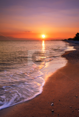 Deserted beach at sunset stock photo, Image shows a deserted beach at sunset by Andreas Karelias
