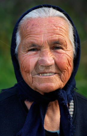Old Greek lady stock photo, Image shows a portrait of an old Greek happy lady, wearing a scarf by Andreas Karelias