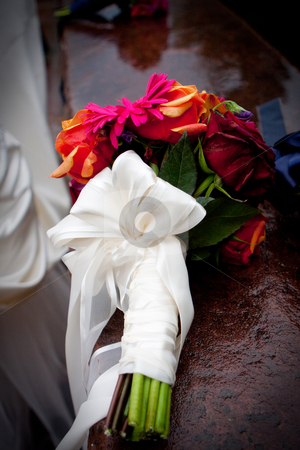 Bridal Bouquet  stock photo, A bridal bouquet of orange, pink and red flowers rests on a ledge by Sharon Arnoldi