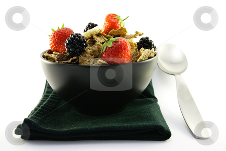 Bran Flakes in a Black Bowl stock photo, Crunchy looking delicious bran flakes and juicy fruit in a black bowl with a spoon on a black napkin on a white background by Keith Wilson