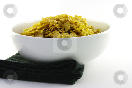 Bowl of Cornflakes and Napkin stock photo, Golden crunchy cornflakes in a round white bowl with a black napkin on a white background by Keith Wilson