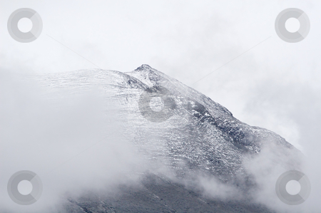 Mountain top stock photo, High mountain top covered partly in first fallen snow. Grey weather. by Anders Peter