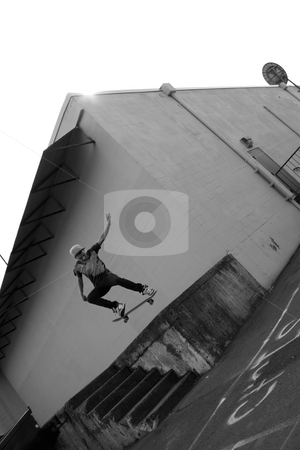 Skateboarder Airborne stock photo, A young skateboarder launches off a concrete loading dock in an urban setting. by Todd Arena