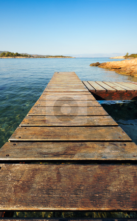 Wooden pier in Greece extending into the sea stock photo, Morning picture of a wooden pier extending into the Aegean Sea,  leading the viewer towards the small islands in the background. Space for text on top. by Andreas Karelias