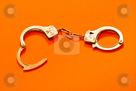 Handcuffs stock photo, Open metal handcuffs on the orange background by Gennady Kravetsky