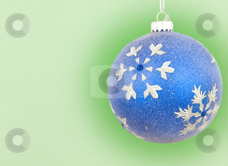 Chirstmas ornament hanging stock photo, Blue bauble ornament hanging with green background by John Teeter