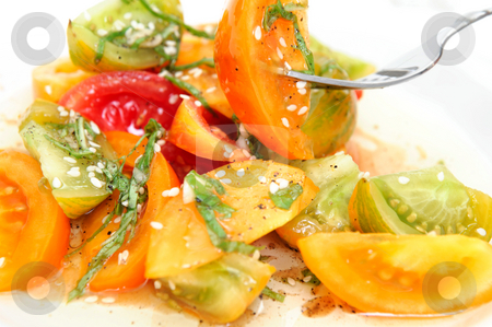 Heirloom Tomato Salad stock photo, Different types of heirloom tomatoe wedges with thinly sliced basil leaves, sesame seeds and an olive oil and raspberry vinegar dressing by Lynn Bendickson