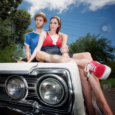 Hipster Couple stock photo, Hippie on the Hood of an old Car by Scott Griessel