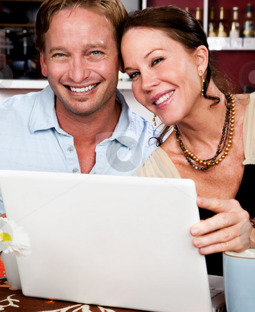 Attractive couple with laptop computer stock photo, Attractive couple in cafe with laptop computer by Scott Griessel