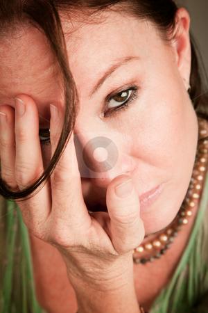 Sad woman covering her face stock photo, Sad woman covering her face with a hand by Scott Griessel