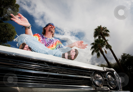 Hippie Meditating on Car Hood stock photo, Hippie Meditating on Hood of Vintage Car by Scott Griessel