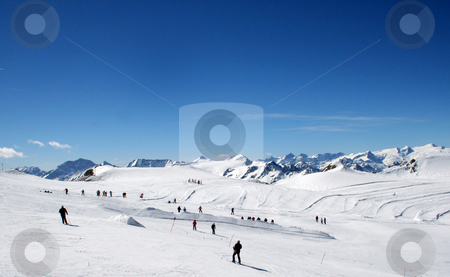 Skiers on mountainside stock photo, Skiers on snowy mountainside under blue sky, Switzerland. by Martin Crowdy