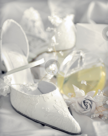 White wedding bridal shoes stock photo, White bridal wedding shoes next to decorative rose. by Martin Crowdy