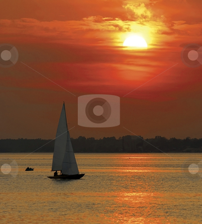 Yacht sailing at sunset stock photo, Orange sunset with sailing yachts silhouetted in foreground, ocean scene. by Martin Crowdy