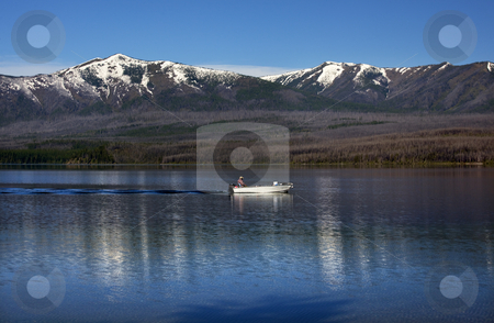 Lake McDonald Fishing Boat Glacier National Park Montana stock photo, Lake McDonald Going Fishing Outboard in front of Snow MountainS Glacier National Park Montana by William Perry