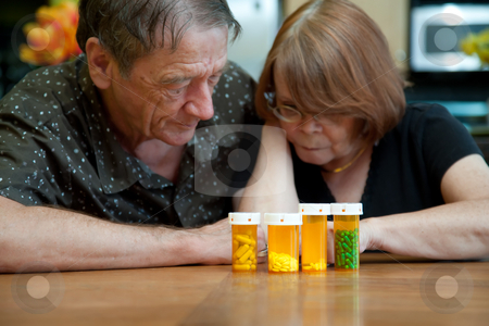 Senior Couple at Home Reading Prescription Labels stock photo, Senior Couple at Home Reading Prescription Bottle Labels by Scott Griessel