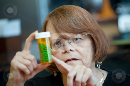 Senior Woman at Home with Prescription stock photo, Senior woman examining prescription bottle with green capsules by Scott Griessel