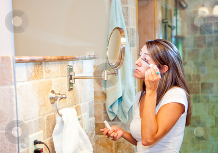 Woman putting on makeup stock photo, A beautiful young woman using a mirror to put on makeup in the bathroom by Sharon Arnoldi