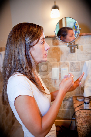 Woman putting on makeup stock photo, A beautiful young woman putting on makeup in the bathroom by Sharon Arnoldi
