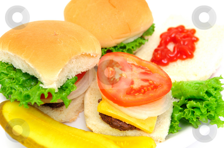 Mini-burgers stock photo, Clodeup of three mini-hamburgers topped with cheddar cheese, white onion, tomato and lettuce on a white plate with sliced dill pickels on the side isolate on a white background by Lynn Bendickson
