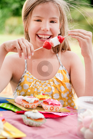 Smiling girl and a stick full of marshmallows stock photo, Teenagers having a great time in the park by Frenk and Danielle Kaufmann