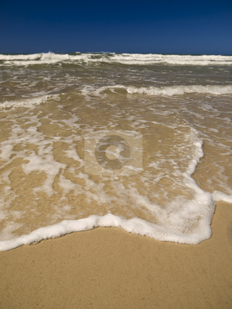 Waves at the beach stock photo, A small wave is coming to the beach sand. by Ignacio Gonzalez Prado