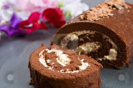 Homemade chocolate roll with fresh flowers stock photo, Homemade chocolate roll with fresh flowers on a slate by Robert Anthony