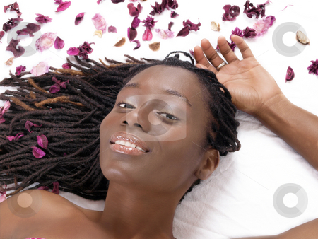 Young black woman reclining on sheet with flower petals stock photo, Young smiling african american woman reclining with flower parts by Jeff Cleveland