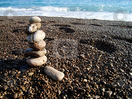 Stone beach stock photo, Stones tower on the coast line of mediterranean beach by Marc Torrell