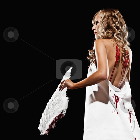 Female Model as Fallen Angel stock photo, A young, adult female model is posed, three quarter length viewable and draped in white fabric. The angle is rear view and she looking away from the camera. She is holding wings that she has taken from her back as indicated by bloody back wounds. The shot is in a square format. by Media Deva